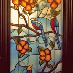 חלון צבעוני עם ציפורים פרחים ופרפרים